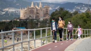 positive news Children in face masks by a beach in Mallorca