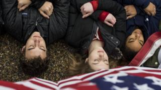 銃規制強化を求め、ホワイトマウス前で死体を模して横たわり抗議する若者たち(19日、ワシントン)