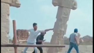 Screengrab from a viral video showing three men shoving a pillar in Hampi