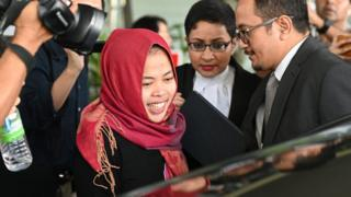 Siti Aisyah surrounded by reporters