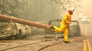 A firefighter steps over a downed power line as he surveys abandoned burned cars on the side of the road after the Camp fire tore through the area in Paradise, California, 10 November 2018