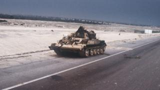 A Chinese-made Type 653 armoured recovery vehicle abandoned by Iraqi troops sits on the side of the road into Kuwait City during the ground phase of Operation DESERT STORM.