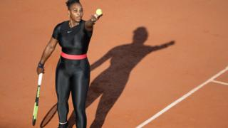Serena Williams in a black cat suit holding a racket and tennis ball