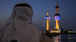 A man looking at the projection of New Zealand flag in Kuwait