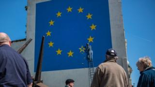 People view a recently painted mural by British graffiti artist Banksy, depicting a workman chipping away at one of the stars on a European Union (EU) themed flag