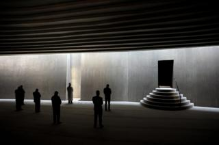 Люди молятся в современном здании