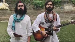 A screengrab from the video shows two bearded male musicians, one holding a guitar