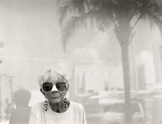 An elderly woman with big sunglasses looks to the camera