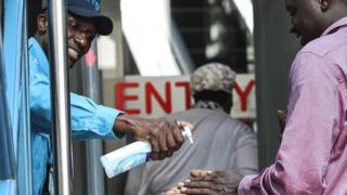 in_pictures A security guard gives hand disinfectant to visitors as precaution measures at an entrance of building in Nairobi, Kenya - 13 March 2020