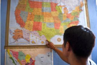 Migrante señala mapa de EE.UU., bajo la cual tiene una de México.