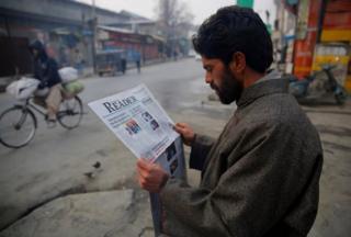 A man reading Kashmir Reader