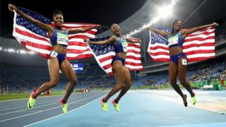 Bronze medallist Kristi Castlin, gold medallist Brianna Rollins and silver medallist Nia Ali of the United States celebrate with American flags after the Women's 100m hurdles final.