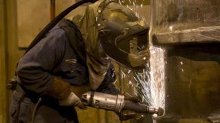 A grinder works on a freshly cast piece of steel in a foundry in Sheffield