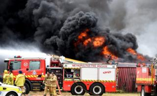 Firefighters and engines in front of the tyre blaze