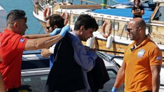 Paramedics escort migrants after being rescued at the port of Mytilene on the island of Lesbos, Greece, 13 July
