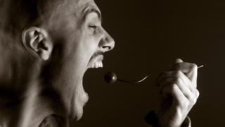 Man eats food on fork hungrily