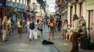 Stock image of musicians playing Irish folk music on the sunny streets of Galway
