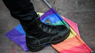 A Turkish anti-riot police officer steps on a rainbow flag during a rally staged by the LGBT community in Istanbul (19 June 2016)