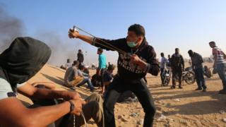 Un palestino lanza una piedra en la frontera entre Israel y Gaza