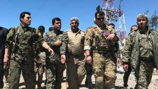 A US military commander (2nd R) walks with Kurdish fighters from the People's Protection Units (YPG) at the YPG headquarters that was hit by Turkish airstrikes in Mount Karachok near Malikiya, Syria April 25, 2017.
