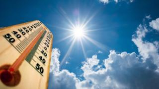 Termômetro e sol vistos de ponto de vista de baixo para cima