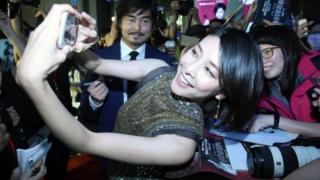 Yuko Takeuchi, pictured taking a selfie with fans, in 2018