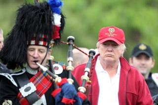 Donald Trump next to a man playing bagpipes at the opening of The Trump International Golf Links Course in July 2012
