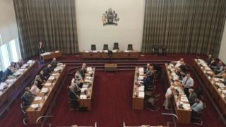 Councillors take part in a meeting in the council chamber