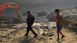 "Two men walk past the ""mud lake"" caused by the landslide in Kachin, with vehicles emerging from the mud"