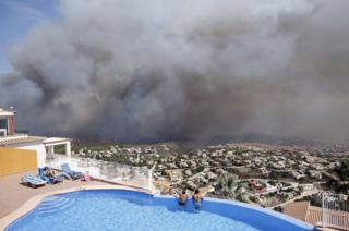 Two men look at a wildfire from a swimming pool as it burns nearby Benitachell village, eastern Spain,