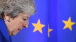 Theresa May stands in front of the EU flag