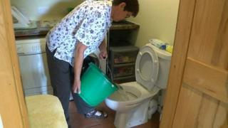 Helen Rees puts a bucket of water into the toilet