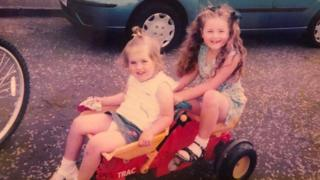 two girls sitting on go-cart