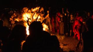 Participants and onlookers gather around a fire