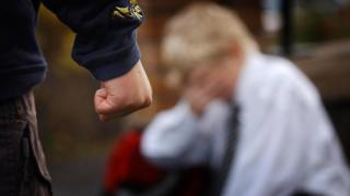 A bully clenches his fist while his victim is seen in the background