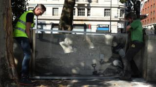 Glass casing being installed around Banksy mural