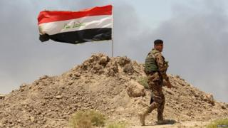 A soldier walks past an Iraqi flag in Husaybah, in Anbar province July 22, 2015.