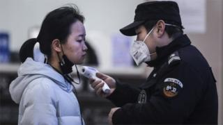 중국 우한에서 보안요원이 보행자의 체온을 측정하고 있다