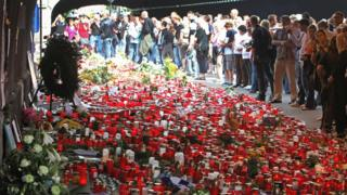 This file photo taken on July 31, 2010 shows people mourning in front of a makeshift memorial of candles and flowers at the site where the 21 Love Parade victims died in Duisburg, western Germany.