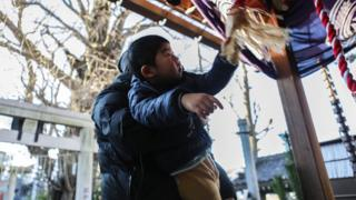 Japanese man helps son to ring a bell