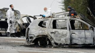 French police officers search through the burnt-out cars