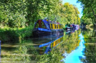 Canal boats reflected in the river