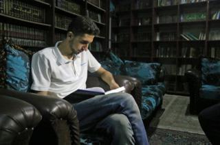 Joven leyendo en la biblioteca secreta de Siria.