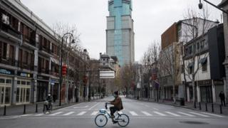 A man by bicycles past an empty street on February 8, 2020 in Wuhan, Hubei province, China.