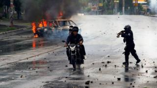 A riot police officer fires his shotgun towards two men during a protest against Nicaragua's President Daniel Ortega's government in Managua, Nicaragua May 28