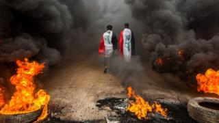 Anti-government protesters wearing Iraqi flags walk past burning tyres in Basra, Iraq (17 November 2019)