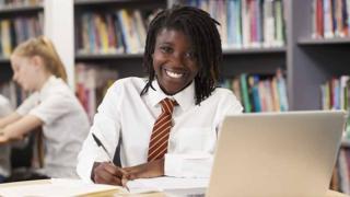 Girl at her desk, smiling