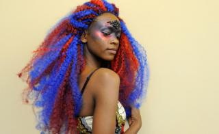 A Rwandan woman with blue and red hair at the 3018: fashion show at the 12th Annual Black New England Conference at the University of New Hampshire - Saturday 20 October 2018