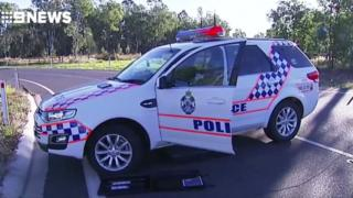 A police car forms part of a roadblock in Queensland