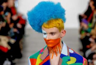 A model with face paint and a blue wig